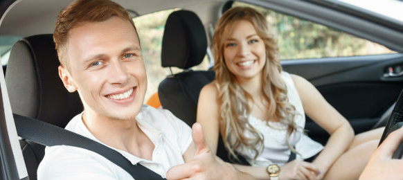 smiling couple posing inside their new car