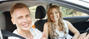 happy couple posing inside their car hire in revesby