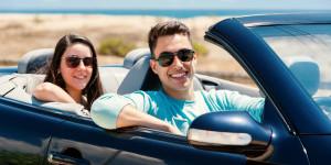 cute couple riding a convertible car