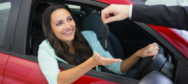 excited woman receives her new car keys