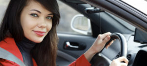 woman in red driving a hire car