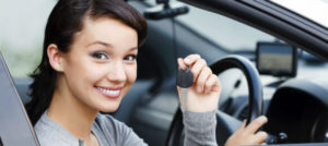 young woman showing keys of her carhire