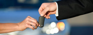 car rental personnel is giving the car key to the customer