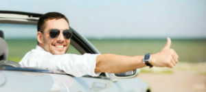 cheerful man driving a car and thumbs up