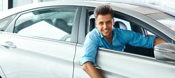 smiling guy posing inside his new car