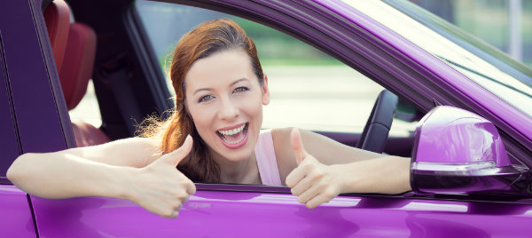 happy woman making a thumbs up while inside her car hire in melton